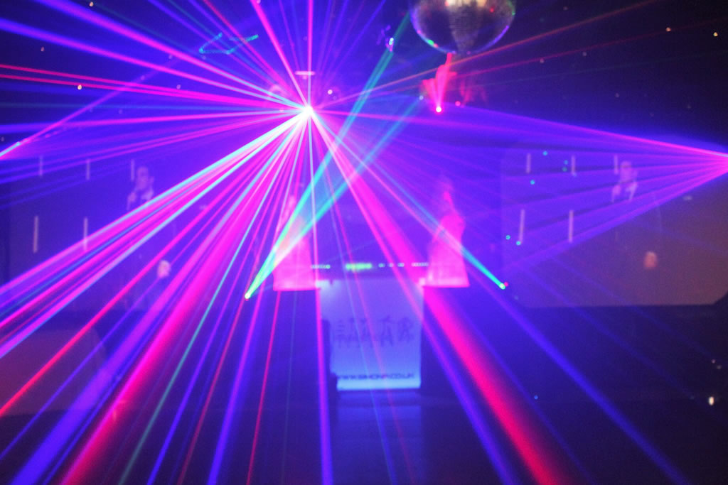 example of lighting equipment for hire at one of Simon P events, with DJ booth in background lit up next to the dance floor