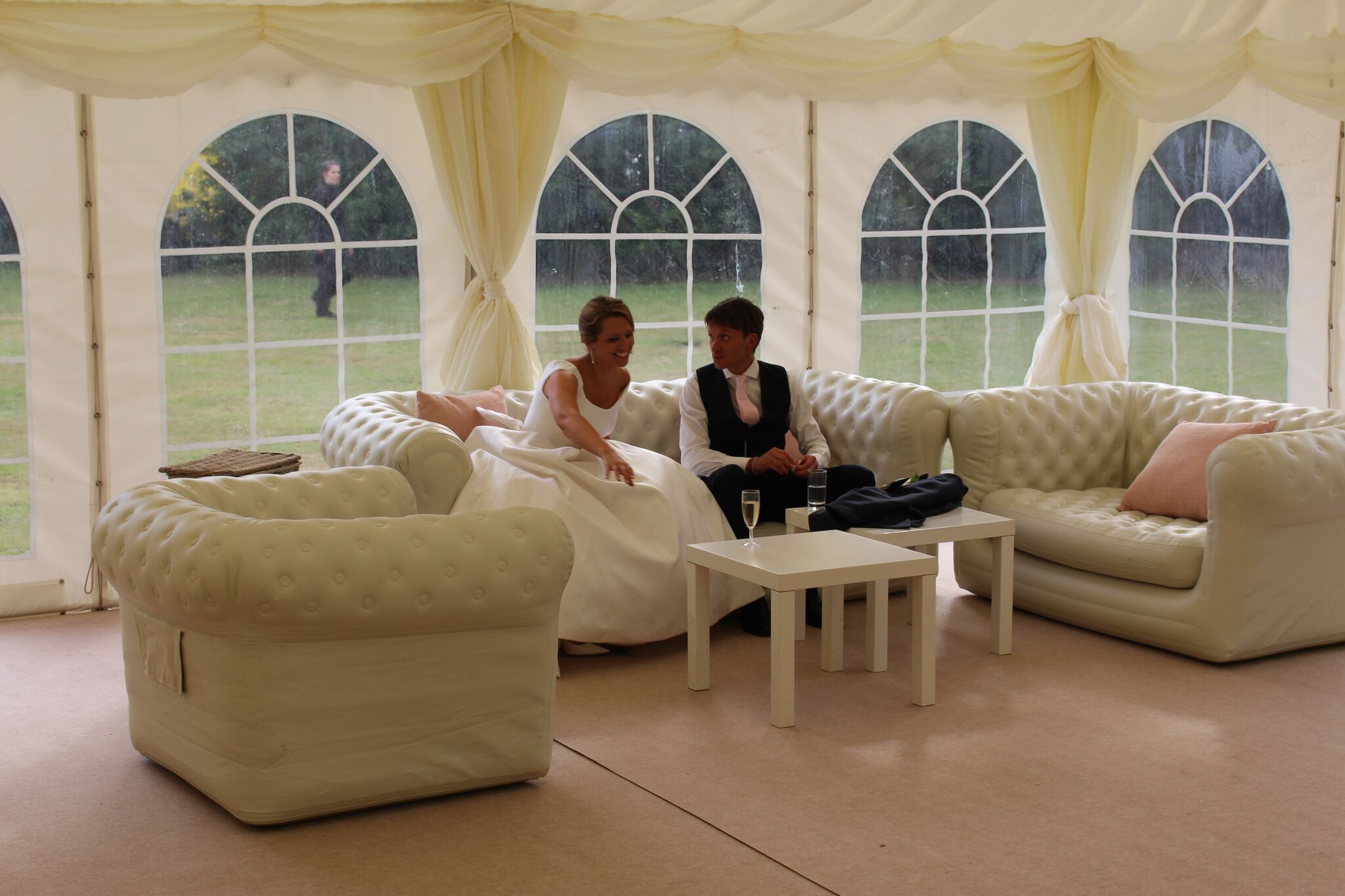 wedding furniture for hire in Surrey, bride and groom having a drink of champagne to celebrate on inflatable sofas